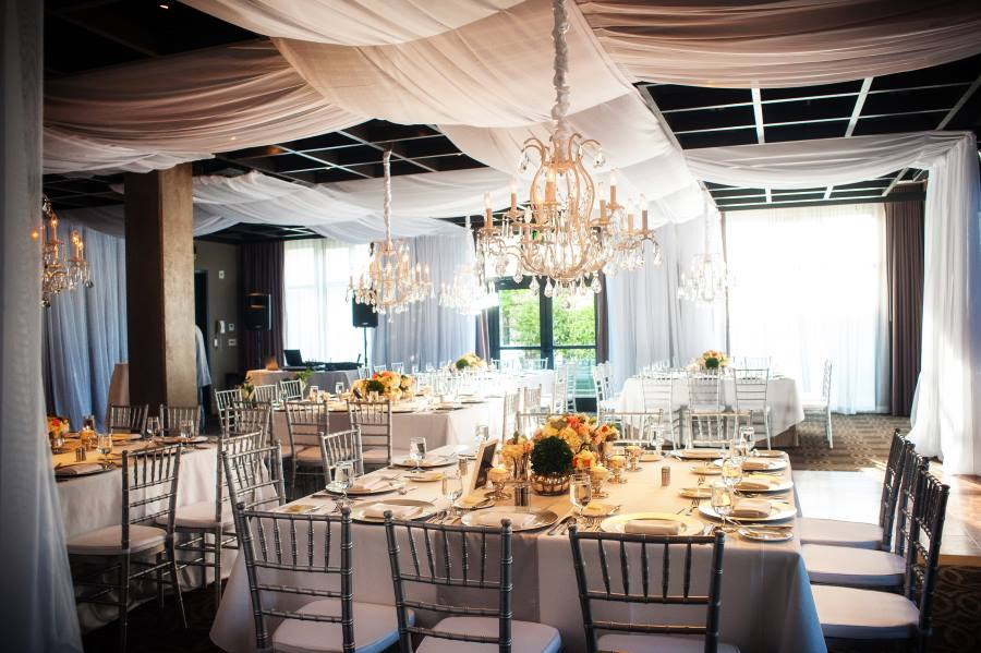Revolution Reception with white drapes and linens and crystal chandeliers