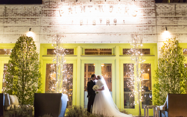 Gatsby Winter Wedding at Proximity Hotel, Bride and Groom in front of Print Works Bistro